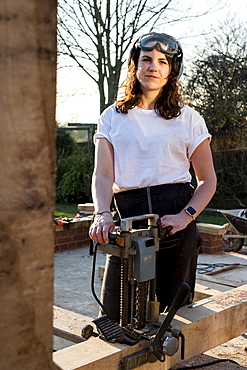 Woman wearing protective goggles holding machine, working on wooden building frame, Oxfordshire, England