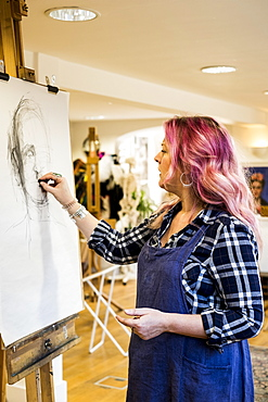 Woman with long blond wavy hair with pink streaks wearing apron standing at an easel, drawing a portrait, Oxfordshire, England
