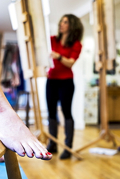 Close up of a bare female foot with red varnished toenails, a model at a life drawing class at art school. An artist working in the background, Oxfordshire, England