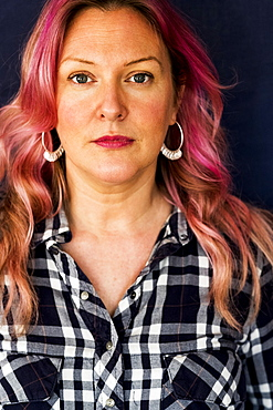Portrait of woman with long blond wavy hair with pink streaks wearing black and white checked shirt and hoop earrings, Oxfordshire, England