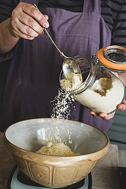 High angle close up of person pouring sugar into mixing bowl with baking ingredients, England