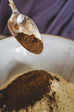 High angle close up of person pouring cocoa powder into mixing bowl with baking ingredients, England