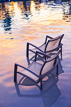 Beach chair in pool at sunset, Grand Cayman, Cayman Islands