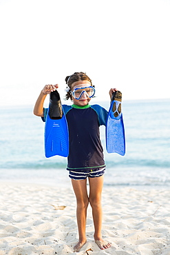 A young boy wearing a snorkel mash and holding up his blue flippers, Grand Cayman, Cayman Islands