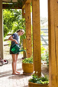 A teenage girl watering plants on a terrace