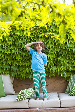 5 year old boy standing in front of green leaves