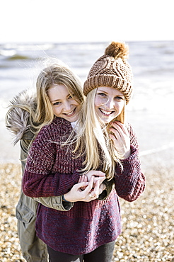Two girls on the beach in winter, Hampshire, England