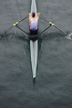 Overhead view of an oarsman in a single scull boat on calm water mid stroke, motion blur