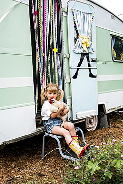 Blond girl holding white chicken sitting outside a caravan