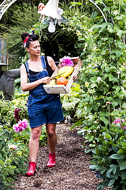 Woman walking in a garden, carrying wooden crate with fresh vegetables and flowers