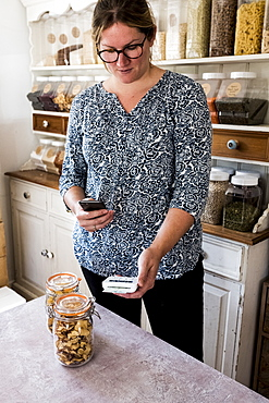 Woman standing in a kitchen, a glass jar with dried fruits, holding card reader and mobile phone, fulfilling an order