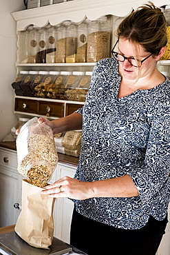 Woman standing in kitchen, pouring oats into paper bag