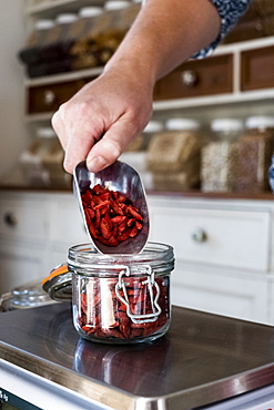 Close up of person weighing Goji berries in glass jar on kitchen scales