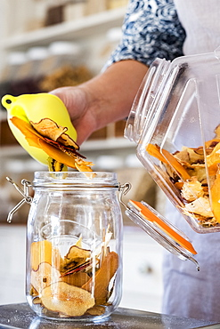 Close up of person standing in a kitchen, placing slices of dried fruit into glass jar