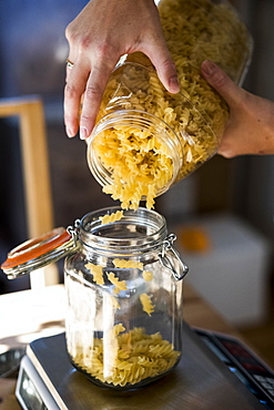 Close up of person pouring Fusilli pasta into glass jar on kitchen scales