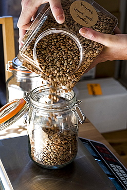Close up of person pouring brown lentils into glass jar on kitchen scales