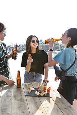 Young Japanese man and two women standing on a rooftop in an urban setting, drinking beer, Fukuoka, Kyushu, Japan
