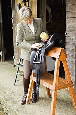 A woman cleaning and preparing tack and saddle, in the courtyard of a riding stable, Riding Stables, Hampshire, England