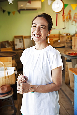 Smiling Japanese woman standing in a farm shop, looking at camera, Kyushu, Japan