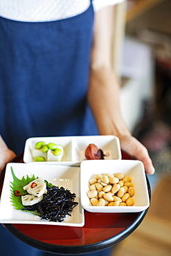 High angle close up of waitress holding a selection of vegetarian Japanese foods in a cafe, Kyushu, Japan