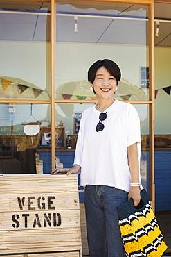 Japanese woman standing outside a farm shop, holding shopping bag, smiling at camera, Kyushu, Japan