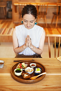 High angle view of Japanese woman sitting in front of a selection of vegetarian food in a cafe. , Kyushu, Japan