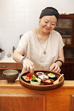 Japanese woman preparing fresh vegetables in a vegetarian cafe, Kyushu, Japan