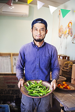 Smiling Japanese man wearing cap standing in farm shop, holding bowl with fresh okra, Kyushu, Japan