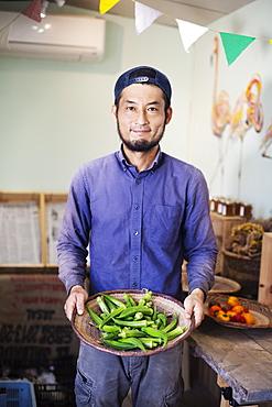 Smiling Japanese man wearing cap standing in farm shop, holding bowl with fresh okra, Kyushu, Japan