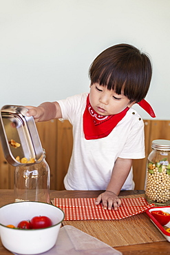 Japanese boy standing at a table in a farm shop, helping prepare food, Kyushu, Japan