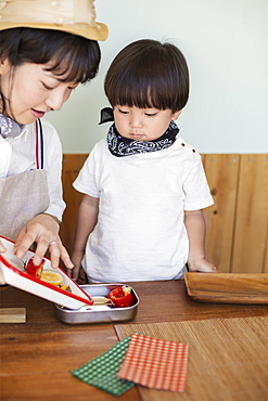 Japanese woman and boy standing in a farm shop, preparing food, Kyushu, Japan