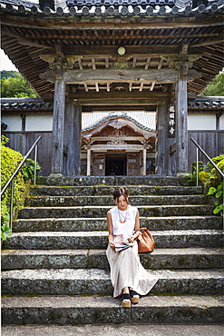 Japanese woman sitting on steps outside a Buddhist temple, Kyushu, Japan