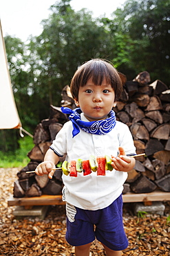 Portrait of Japanese boy holding skewer with fresh kiwi and melon, looking at camera, Kyushu, Japan