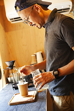 Japanese man wearing baseball cap and glasses standing in an Eco Cafe, preparing cup of coffee, Kyushu, Japan