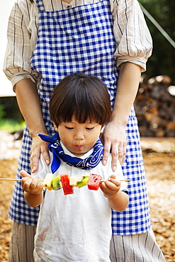 Japanese woman and boy standing outdoors, holding skewer with fresh kiwi and melon, Kyushu, Japan