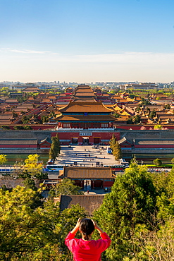 Young woman taking photograph of view over Forbidden City in Beijing, China, Beijing, China