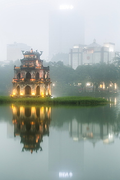 Exterior of illuminated temple reflected in a lake at dusk, skyscraper in the distance, Vietnam