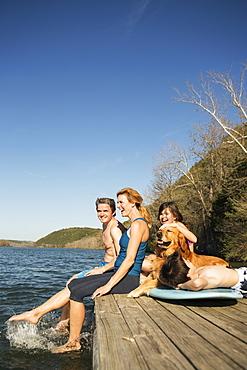 A family and their retriever dog on a jetty by a lake, Austin, Texas, USA
