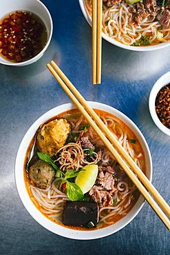 High angle close up of bowl of Bun Bo Hue with beef, crab balls, blood sausage and herbs, Vietnam