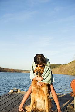 A girl cuddling a golden retriever dog, Austin, Texas, USA