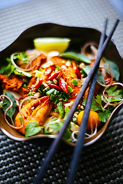 High angle close up of chopsticks on bowl with Asian food containing noodles, prawns, vegetables and chili garnish, Vietnam