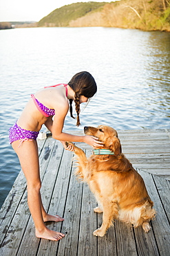 A girl in a bikini with a golden retriever dog lifting its paw up, Austin, Texas, USA