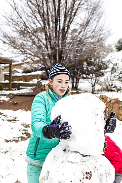 A teenage girl building a snowman, United States