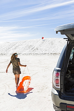 Teenage girl with a sled on white sand dunes, White Sands National Monument, New Mexico, United States