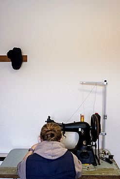Rear view of female saddler sitting in workshop, sewing on saddlery sewing machine, Berkshire, United Kingdom