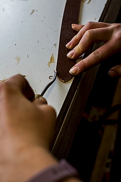 High angle close up of person working in saddler's workshop, using hand tool on leather strap, Berkshire, United Kingdom