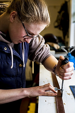 Female saddler standing in workshop, using hand tool on leather strap, Berkshire, United Kingdom