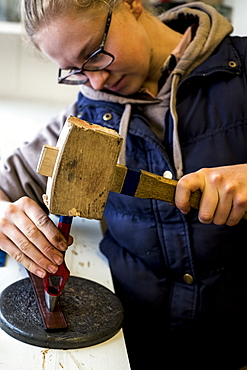 Female saddler standing in workshop, using hand tool and wooden mallet, punching holes into leather strap, Berkshire, United Kingdom