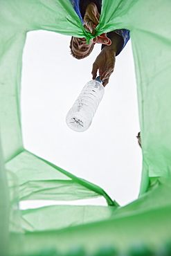 Man dropping a plastic bottle into a green plastic bag, view from inside bag. , Bristol, United Kingdom