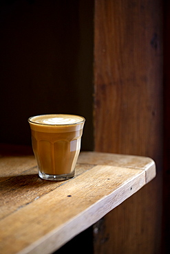 Close up of glass of cafe latte on a rustic wooden table in a cafe